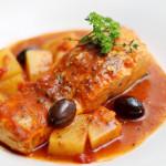 Salmão ao molho de tomate, batatas e azeitonas.